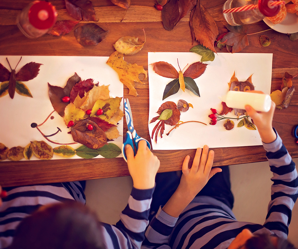 two children creating crafts with leaves