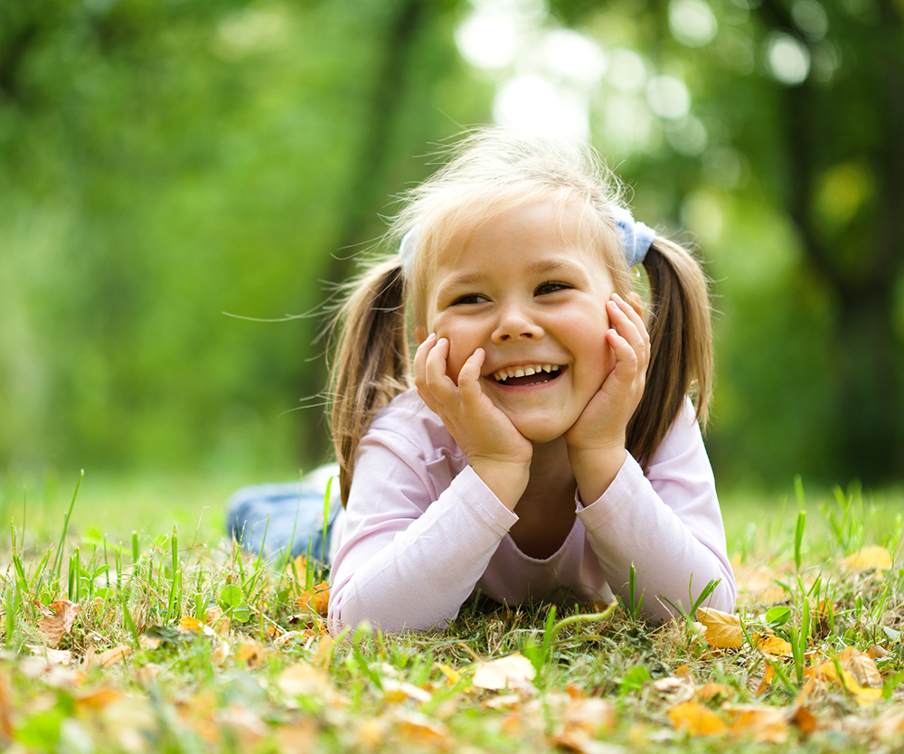 smiling girl laying on grass